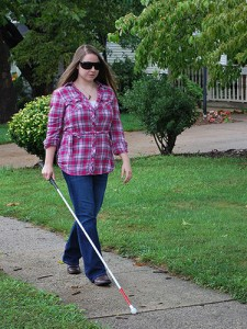 Colleen walking with cane and sunglasses