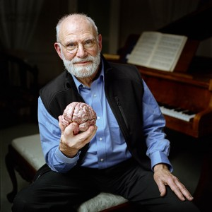 Dr. Oliver Sacks holding a model of a brain and sitting by a piano