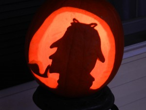 A pumpkin carved with the silhouette of Sherlock Holmes and his pipe