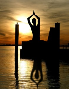 Silhouette of a person meditating near water