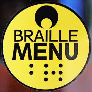 Image of a small yellow sticker with black writing that says Braille Menu and underneath in braille code, the word braille