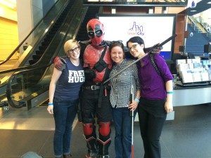Alyssa, Colleen, and Cheryl pose with a someone dressed as Deadpool, who holds a sword near their throats