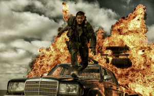 Tom Hardy as Mad Max nearly consumed by an explosion of fire and car parts