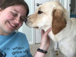 Colleen laughs as Golden yellow puppy Joplin noses her cheek